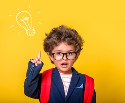 Child boy in eyeglasses isolated on yellow paper wall. Excellent idea, kid with illustrated bulb. Happy smiling kid go back to school, kindergarten. Success, motivation, winner, genius concept.