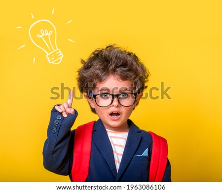 Child boy in eyeglasses isolated on yellow paper wall. Excellent idea, kid with illustrated bulb. Happy smiling kid go back to school, kindergarten. Success, motivation, winner, genius concept. Stock photo ©