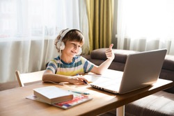 child boy  in headphones  show sight thumbs up, is using a laptop and communicates on the Internet  at home. homeschooling, distant learning, online e