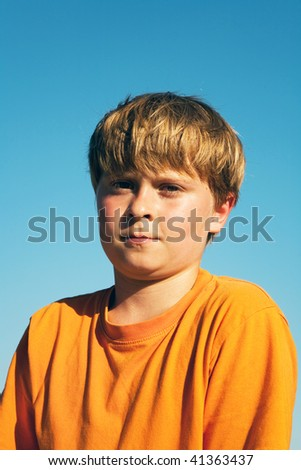 child boy in orange T-shirt  is looking self confident and happy after doing sports