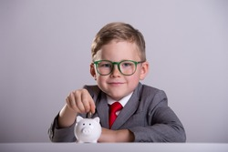 Child boy in suit and glasses putting coin into piggy bank