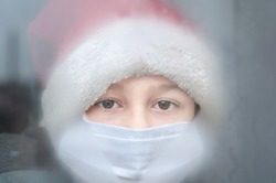 Child boy looks out the misted window wearing a santa claus hat, protective mask. Christmas holidays in quarantine covid-19. Coronavirus epidemic. Waiting. Winter holidays, isolation, New Year at home