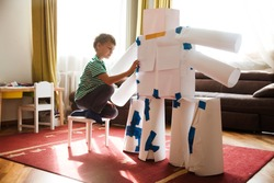 child boy makes a large robot from paper and cardboard. Children's creativity.