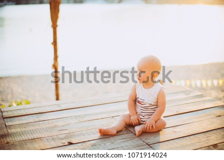 Child boy one year blond sits on a wooden dock, a pier in striped clothes, a compound near the pond on a sandy beach against a background of a river in the summer at sunset of the day.