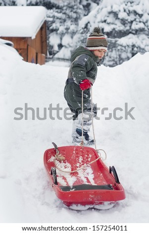 Child boy or girl pulling a sledge in fresh snow in winter