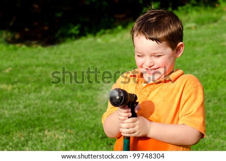 Child, boy or kid plays with water hose outdoors during summer or spring to cool off in hot weather