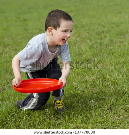 Child boy playing on a grass with a red frisbee disk.