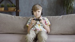 Child boy playing online video game with joystick and headphones seated on a sofa