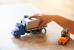 child boy playing toys on table at home / kid hands playing toy car truck