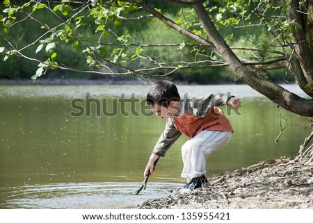 Child boy playing with a stick on the edge of the lake or a river in the nature.