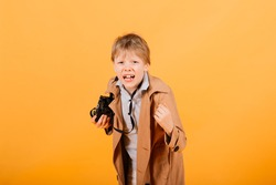 Child boy red head photographer with retro photocamera in a studio