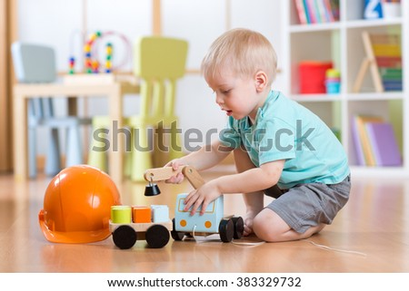 child boy toddler playing with toy car indoors