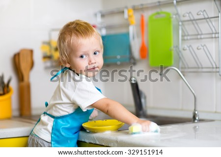 Child boy washing dishes in a domestic kitchen