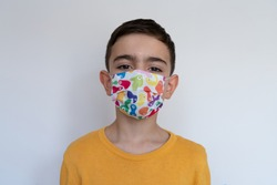 child boy wears colorful protective medical face mask isolated. standing beyond white background portrait photo. boyhood childhood. yellow sweater during coronavirus outbreak. 2021 pandemic lockdown.