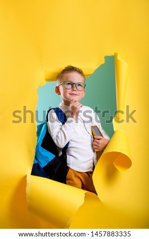 Child boy with book and bag breaking through yellow paper wall. Happy  smiling kid go back to school, kindergarten. Success, motivation, winner, genius concept. Little kid dreaming to be superhero