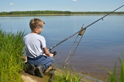 Child boy with fishing rod on the shore of clean lake. Little fisherman spinning on pond. quiet place on the shore of a pond