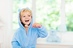 Child brushing teeth. Kids tooth brush and paste. Little baby boy in blue bath robe or towel brushing his teeth in white bathroom with window on sunny morning. Dental hygiene and heath for children.