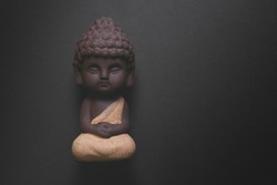 Child Budha statue on a black background
