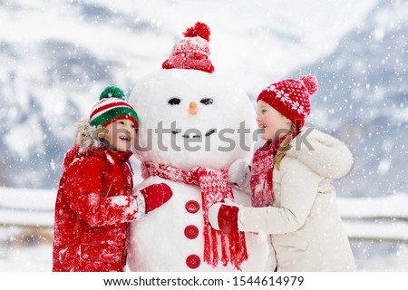 Child building snowman. Kids build snow man. Boy and girl playing outdoors on snowy winter day. Outdoor family fun on Christmas vacation in the mountains. Children play in Swiss mountain landscape. #1544614979