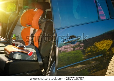Child Car Safety Seat. Orange Car Seat Inside Small Family Van.
