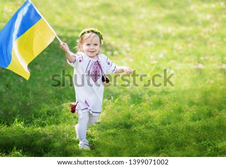 Child carries fluttering blue and yellow flag of Ukraine in field. Ukraine's Independence Day. Flag Day. Constitution day. Girl in traditional embroidery with flag of Ukraine #1399071002