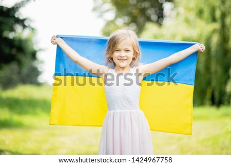 Child carries fluttering blue and yellow flag of Ukraine in field. Ukraine's Independence Day. Flag Day. Constitution day. Girl in traditional embroidery with flag of Ukraine #1424967758