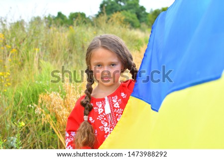 Child carries fluttering blue and yellow flag of Ukraine in field. Ukraine's Independence Day. Flag Day. Constitution day. Girl in traditional embroidery with flag of Ukraine #1473988292