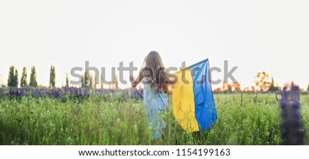 Child carries fluttering blue and yellow flag of Ukraine in lupine field. Ukraine's Independence Day. Flag Day #1154199163