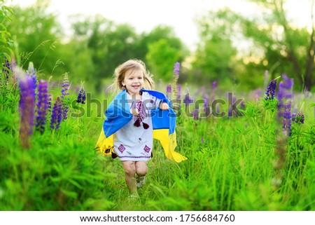Child carries fluttering flag of Ukraine in field. Ukraine's Independence Day. Flag Day. Constitution day. Girl in traditional embroidery with flag of Ukraine Foto stock ©