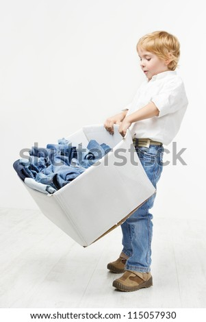 Child carrying cardboard box packed with jeans. Kids clothing fashion. White background.