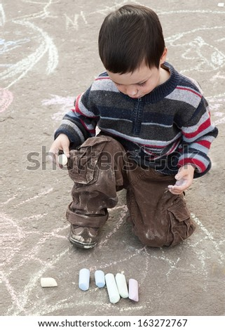Child chalk drawing on the pavement outside.