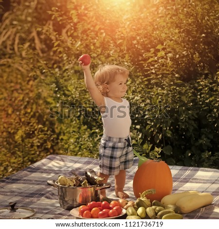Child Childhood Children Happiness Concept. One small smiling child at picnic with ladle holding red tomato standing near pot orange pumpkin squash and cucumber on checkered plaid on natural