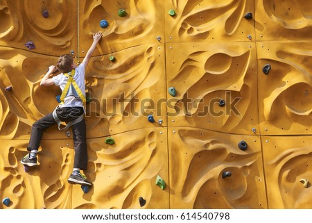 child climbing a rock wall...