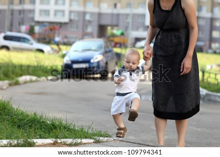 Child climbing on sidewalk with mother's support - stock photo