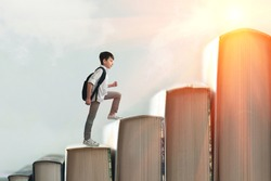 Child climbing stairs made of on sky background. Education or hard study concept. Soft focus