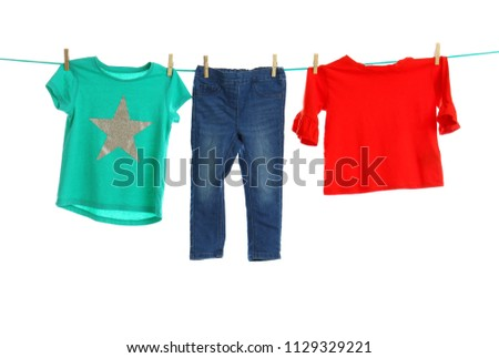 Child clothes on laundry line against white background #1129329221