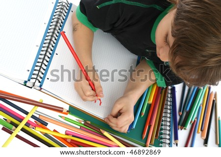 Child coloring with colored pencils, laying on the floor