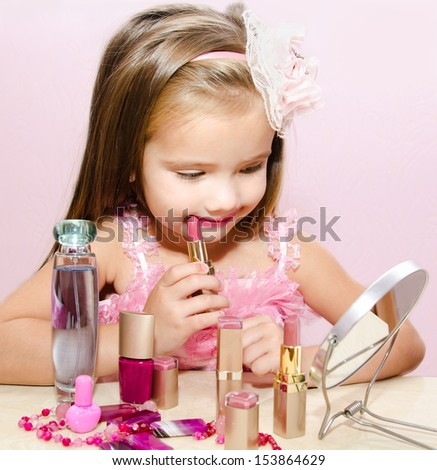 Child cosmetics  Cute little girl with lipstick and  mirror isolated