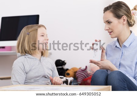 Child counselor discussing drawing with smiling girl during play therapy #649305052