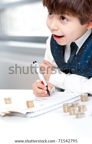 Child counting money and taking notes. Selective focus on the notebook.