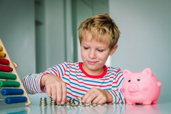 child counting money, boy put coins into piggy bank