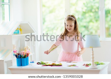 Child creating picture with colorful leaves. Art and crafts for kids. Little girl making collage image with rainbow plant leaf. Biology homework for young school student. Creative autumn home fun.