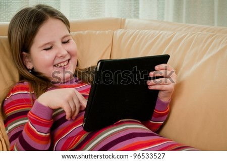 Child (cute girl) playing with tablet at home lying on sofa