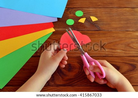 Child cuts a car out of paper. Sheets of colored paper. Kids art. Kids crafts. Crafts concept. How to make a greeting card father\'s day