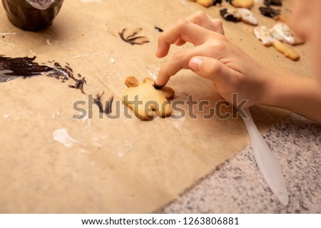 child decorates biscuits with coloured sprinkles and chocolate