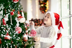 Child decorating Christmas tree at home. Little boy in pajamas with Xmas ornament. Family with kids celebrate winter holidays. Kids decorate living room and fireplace for Christmas.