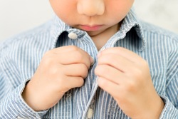 Child Development concept: Close up of a little kindergarten boy's hands learning to get dressed, buttoning his striped blue shirt. Montessori practical life skills - Care of self, Early Education.