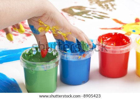 child dipping fingers in painting colors
