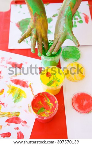 Child dipping fingers in washable, non-toxic finger paints, painting a drawing. Sensory play, innovative approach to learning, fun childhood, back to school concept.