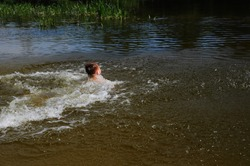 Child dives into the river with a running start. The boy jumps, swims and splashes in the river in the summer time